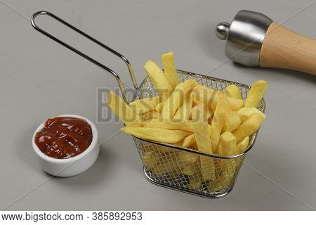 Portion Of Potato Chips In A Metal Basket In A Neutral Background