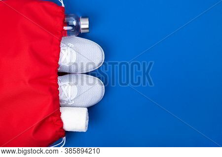 Top View Of White Sport Shoes Sneakers, Reusable Glass Water Bottle And Towel In Red Sport Bag On Bl