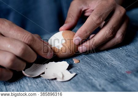 closeup of a young caucasisan man removing the eggshell of a boiled egg on a rustic gray wooden surface