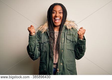 Young african american woman wearing winter parka coat over isolated background celebrating surprised and amazed for success with arms raised and open eyes. Winner concept.