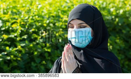 Muslim Woman In A Protective Medical Mask Prays To God. Muslim Woman In A Protective Medical Mask Pr