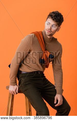 Fashionable Man In Autumn Outfit And Glasses Sitting On Wooden Stool Isolated On Orange