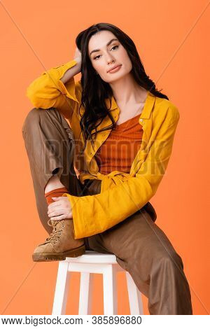 Trendy Woman In Autumn Outfit Sitting On White Stool And Looking At Camera Isolated On Orange
