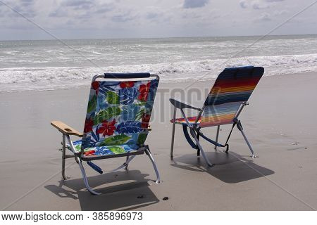 Two Beach Chairs Stand Empty Waiting For Waves To Roll In At The Beach At Emerald Isle,north Carolin
