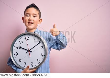 Young little boy kid holding big minute clock over isolated pink background happy with big smile doing ok sign, thumb up with fingers, excellent sign