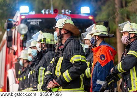 Bavaria / Germany - September 16, 2020: German Firemen Stands Near A Fire Truck During An Exercise