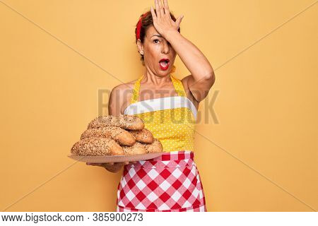 Middle age senior housewife pin up woman wearing 50s style retro dress cooking wholemeal bread stressed with hand on head, shocked with shame and surprise face, angry and frustrated. Fear and upset.