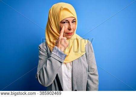 Middle age brunette business woman wearing muslim traditional hijab over blue background Pointing to the eye watching you gesture, suspicious expression