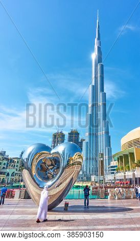 Dubai, UAE - January 30, 2020: The Dubai Steel Heart - Modern sculpture next to Burj Khalifa building and Dubai Mall, United Arab Emirates