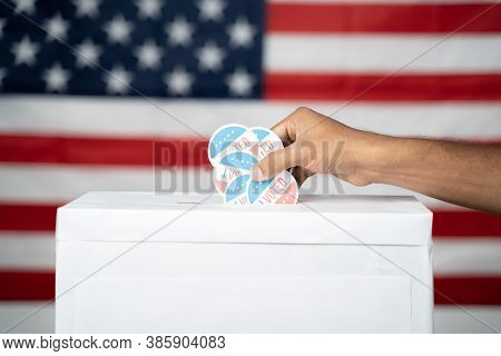 Close Up Of Hands Dropping Multiple I Voted Sticker Inside Ballot Box With Us Flag As Background, Co