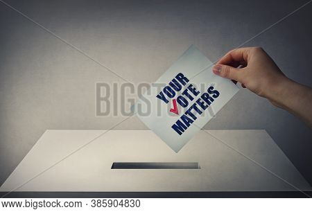 Person At The Polling Station Holding A Ballot Paper In His Hand With The Message Your Vote Matters.