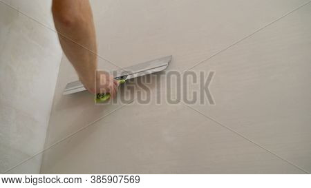 Worker Spackles The Walls With A Spatula. Spatula With Putty In Hand. Worker Puts Of Plaster On Wall
