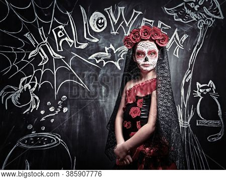 Portrait of a child girl in a costume of Calavera Catrina posing by a chalkboard with Halloween decoration. Little girl with sugar skull makeup. Halloween party. Dia de los muertos. Day of The Dead.