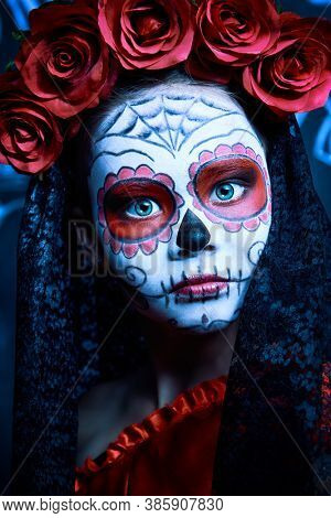 Portrait of a child girl in a costume of Calavera Catrina over vintage background. Little girl with sugar skull makeup. Halloween party. Dia de los muertos. Day of The Dead.