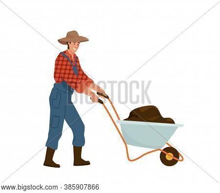Man Farmer Carries Wheelbarrow Full Of Dirt Manure Or Ground. Gardener Wearing In Jumpsuit, Shirt In