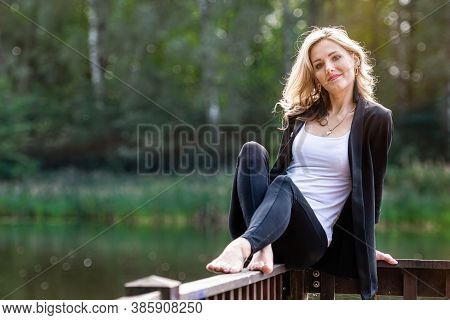 Young Positive, Smiling Woman Sits On The Wooden Railings Of The Pier, Blurred Lake Landscape In The