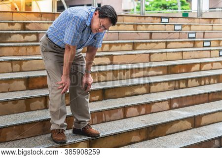 Elderly Man Standing On The Stairs He Is Having Symptoms Pain On Both Sides Of The Knee, Due To Oste