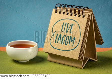 live lagom - Swedish philosophy for a balanced life, handwriting in an art sketchbook with tea, lifestyle concept