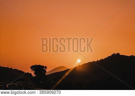 Beautiful Orange Sky Sunset On Highway With Cars Driving Around The Mountains With Sun Above And Ced