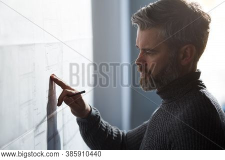 Close-up Portrait Of Handsome Man Concentrated On Work. Architect Working In Office With Blueprints.