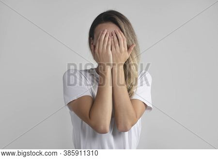 Young European Woman In White T-shirt Hides Her Face With Both Palms, Studio Photo Isolated On Gray