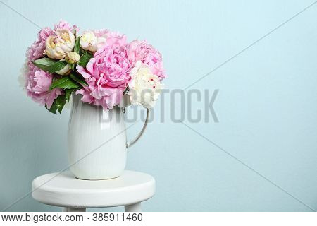 Beautiful Peonies In Jug On White Stool Against Light Blue Background. Space For Text