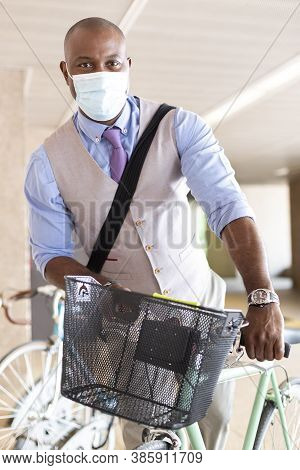 Black Entrepreneurial Man Parking His Bike. He Is Wearing A Medical Mask And Formal Wear. Concept Of