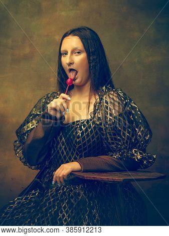 Candy. Young Woman As Mona Lisa, La Gioconda Isolated On Dark Green Background. Retro Style, Compari