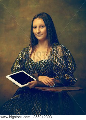 Tablet Scrolling. Young Woman As Mona Lisa, La Gioconda Isolated On Dark Green Background. Retro Sty