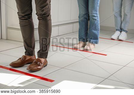 People Standing In Line Behind Taped Floor Markings For Social Distance Indoors, Closeup. Coronaviru