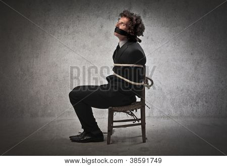 Businessman tied to a chair and gagged