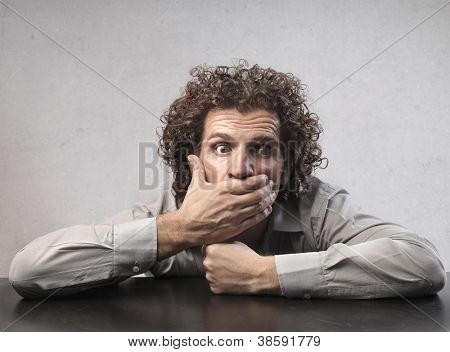 Surprised businessman putting his hand to his mouth