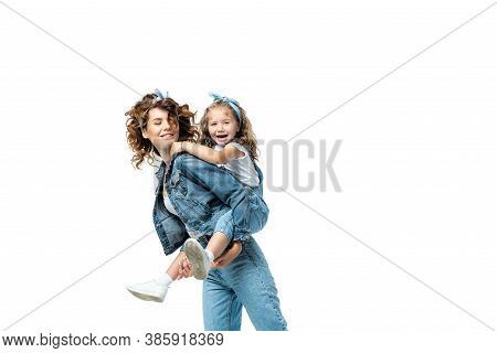 Side View Of Mother Piggybacking Daughter In Denim Outfit Isolated On White
