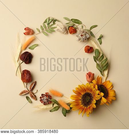 Dried Flowers And Leaves Arranged In Shape Of Wreath On Beige Background, Flat Lay With Space For Te