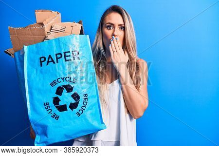 Young beautiful blonde woman recycling holding paper recycle bag full of paperboard covering mouth with hand, shocked and afraid for mistake. Surprised expression