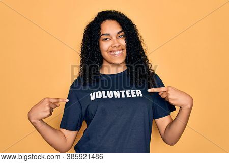 Young african american curly woman doing volunteering wearing volunteer t-shirt very happy pointing with hand and finger