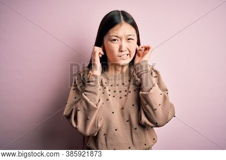 Young beautiful asian woman wearing fashion and elegant sweater over pink solated background covering ears with fingers with annoyed expression for the noise of loud music. Deaf concept.