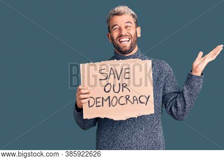 Young blond man holding save our democracy cardboard banner celebrating victory with happy smile and winner expression with raised hands