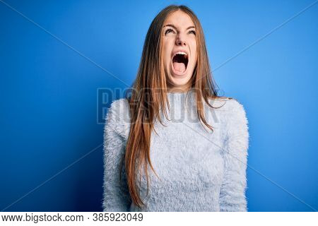 Young beautiful redhead woman wearing casual sweater over isolated blue background angry and mad screaming frustrated and furious, shouting with anger. Rage and aggressive concept.