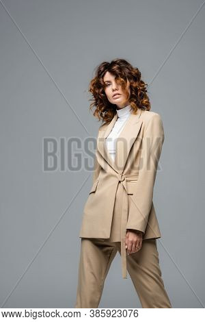 Elegant Woman In Beige Suit Posing Isolated On Grey
