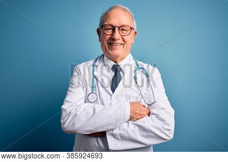 Senior grey haired doctor man wearing stethoscope and medical coat over blue background happy face smiling with crossed arms looking at the camera. Positive person.