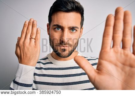 Handsome man with beard showing alliance ring marriage on finger over white background with open hand doing stop sign with serious and confident expression, defense gesture