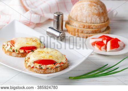 Gourmet Sandwiches With Crab Salad, Fresh Tomatoes And Cheese On A Plate On A White Wooden Table. De