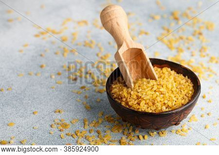 Raw Uncooked Bulgur (crushed Wheat Dry Groats) In A Clay Bowl On A Grey Concrete Background. A Veget