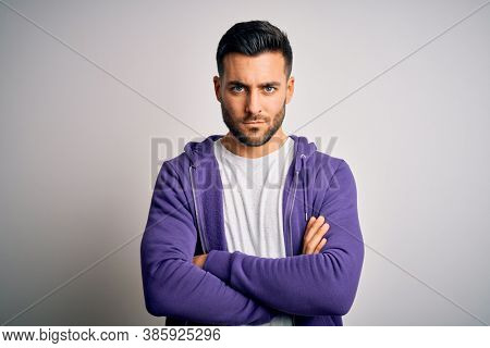 Young handsome man wearing purple sweatshirt standing over isolated white background skeptic and nervous, disapproving expression on face with crossed arms. Negative person.