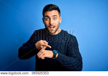 Young handsome man wearing casual sweater standing over isolated blue background In hurry pointing to watch time, impatience, upset and angry for deadline delay