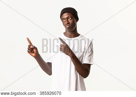 Portrait Of Skeptical Or Disappointed Sassy African-american Guy, Wearing Beanie, Pointing Fingers U