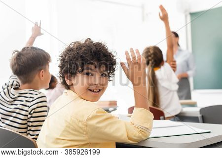 Selective Focus Of Arabian Schoolboy With Hand In Air Looking At Camera Near Multicultural Classmate