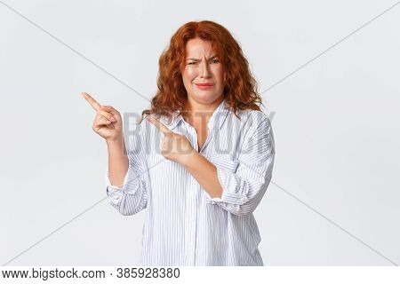 Skeptical And Judgemental Redhead Middle-aged Woman Pointing Upper Left Corner And Grimacing From So