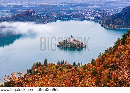 Aerial View Of Church Of Assumption In Lake Bled, Slovenia In The Aurumn With Colorful Trees